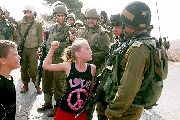 Palestinian girl, wearing a t-shirt with a peace sign, stands up to ...