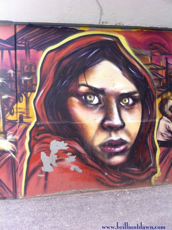 "A mural of   ""the Afghan Girl"" done with spray paint. Mural found in the heart of Toronto's Kensington Market/Chinatown (I think on Bellevue street corner of Dundas). Artist unknown. Photo taken with my iPhone."
